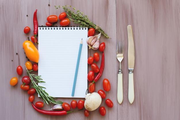 Przepisy na notatniki na drewnianym stole. świeże warzywa.