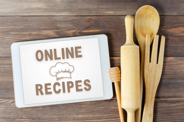 Przepisy online. książka kucharska w komputerze typu tablet. przybory kuchenne. brązowe drewniane tła.