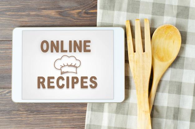 Przepisy online. książka kucharska w komputerze typu tablet. przybory kuchenne. brązowy drewniany stół
