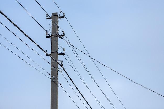 Przeplatanie przewodów elektrycznych ze światłami na tle nieba. sylwetka filaru