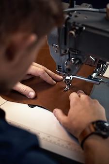 Przepływ pracy rymarza. garbarz lub skinner szyje skóry na specjalnej maszynie do szycia. pracownik szyje na maszynie do szycia, strzał zza mistrza.