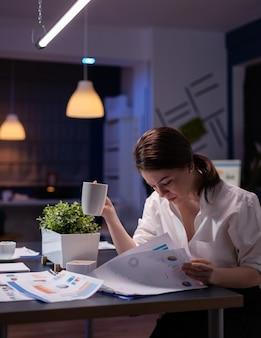 Przepracowana bizneswoman pracuje w godzinach nadliczbowych w sali konferencyjnej biura firmy biznesowej w godzinach wieczornych