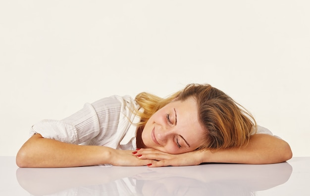 Przepracowana i zmęczona młoda kobieta śpi na des