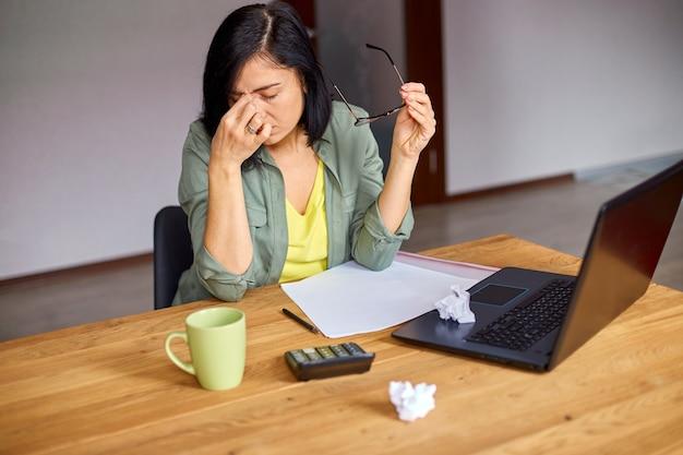 Przepracowana kobieta odczuwa zmęczenie oczu po pracy przy komputerze w domu
