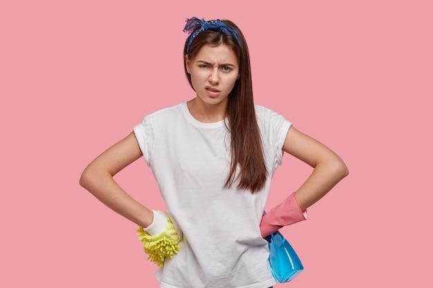 Przepracowana młoda gospodyni domowa czuje się zmęczona, trzyma ręce na talii, nosi casualową koszulkę, opaskę na głowę, gumowe rękawiczki, patrzy z niezadowoleniem