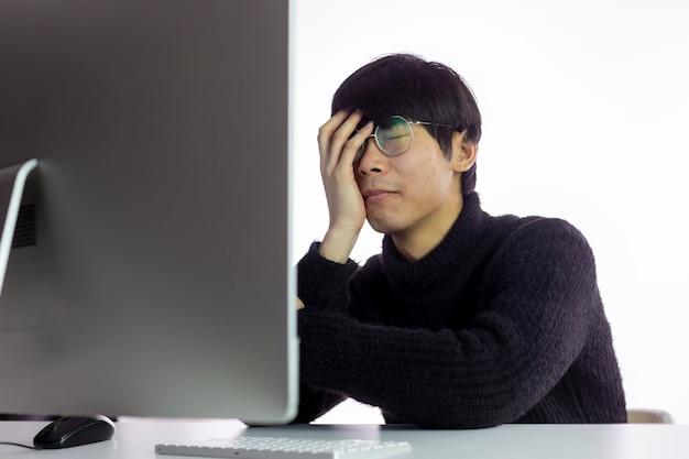 Przepracowani azjaci w biurze, zmęczeni pracą. ręka zakrywa twarz, oczy zamknięte