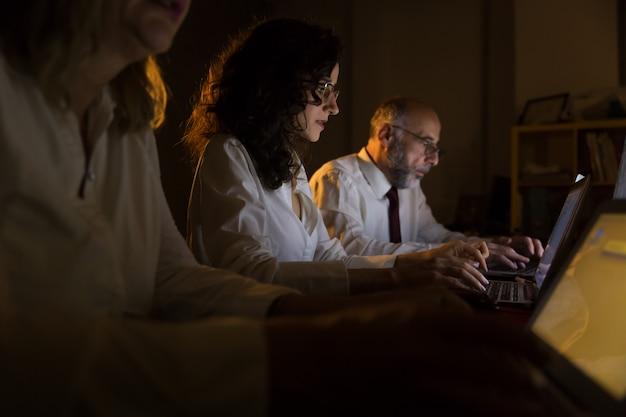 Przepracowani ludzie biznesu za pomocą laptopów