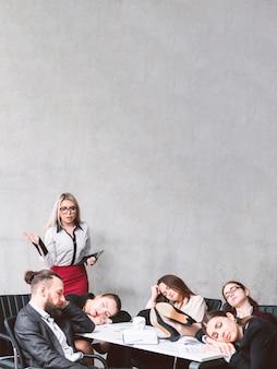 Przepracowanie i obciążenie biznesowe. zdumiony lider zespołu patrzący na kolegów śpiących w miejscu pracy