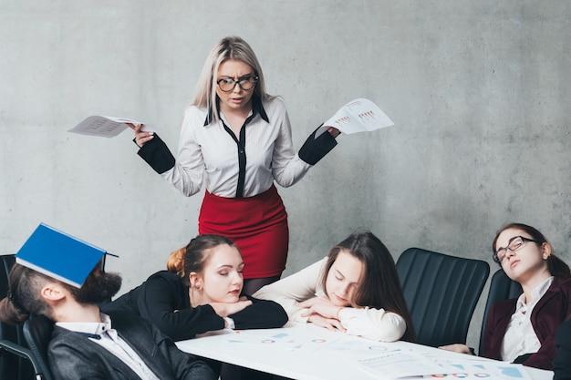 Przepracowanie okresu rozliczeniowego. członkowie zespołu firmy spanie na biurku. zszokowany kolega alarmuje.
