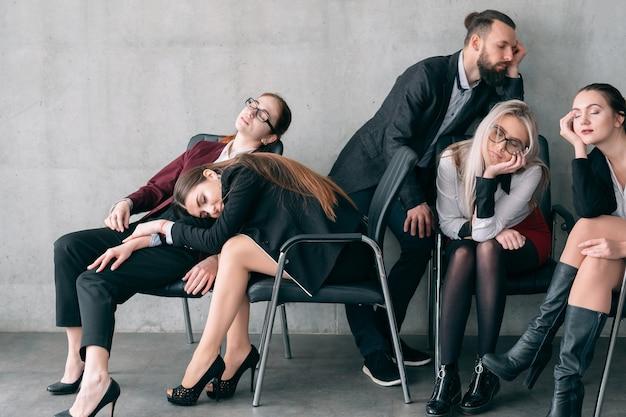 Przepracowanie okresu rozliczeniowego. członkowie zespołu firmy śpi na krzesłach.