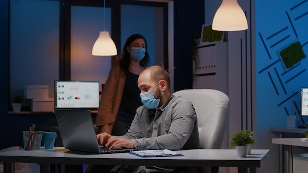 Przepracowany biznesmen z maską na twarz przed covid19 pracującym w biurze startowym sprawdzającym strategię zarządzania późno w nocy. wyczerpany kierownik zostaje sam w pokoju firmy po odejściu kolegi