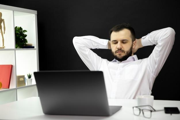 Przepracowany biznesmen z zamkniętymi oczami i rękami na głowie zmęczony pracą