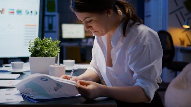 Przepracowany businesswoman pracy w godzinach nadliczbowych w sali konferencyjnej biura firmy biznesowej wieczorem analizując wykresy marketingowe podczas picia kawy. przedsiębiorca ciężko pracujący nad raportami zysków finansowych