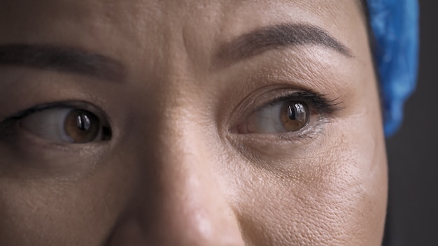 Przepracowany medyk odczuwa stres po długim czasie. super bliska strzał zmęczonych oczu lekarza. kobieta jest ubranym ochronnego kapelusz patrzeje stronę