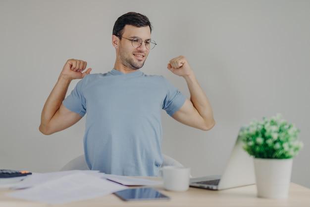 Przepracowany męski freelancer rozciąga się w miejscu pracy, kończy pracę, szczęśliwie patrzy na ekran przenośnego laptopa