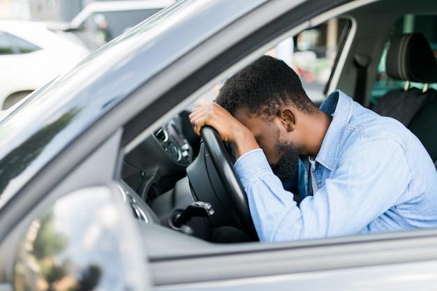 Przepracowany osobisty afrykański kierowca zasypiający na kierownicy samochodu, zmęczony człowiek