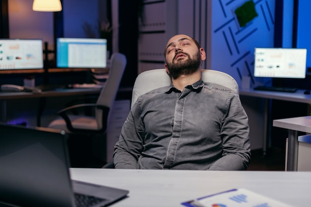 Przepracowany wyczerpany mężczyzna śpi na krześle w pustym biurze. pracoholik zasypia z powodu pracy do późnych godzin nocnych sam w biurze przy ważnym dla firmy projekcie.