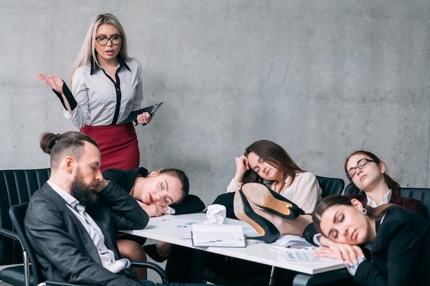 Przepracowany zespół. roczny raport biznesowy. zdumiony lider zespołu patrzący na kolegów śpiących w miejscu pracy.