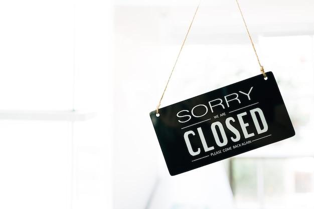 Przepraszamy i zamknięta tablica szyldowa przez szyby drzwi w kawiarni z czystym białym wnętrzem