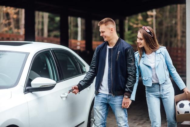 Przeprowadzka do nowego budynku, para jedzie do nowego domu w pobliżu białego samochodu.