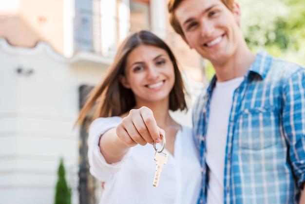Przeprowadzka do nowego domu. piękna młoda kochająca para stojąca przed domem, podczas gdy kobieta trzyma klucz i uśmiecha się