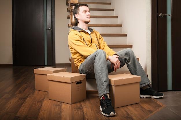Przeprowadzka. młody człowiek z kartonami na schodach.