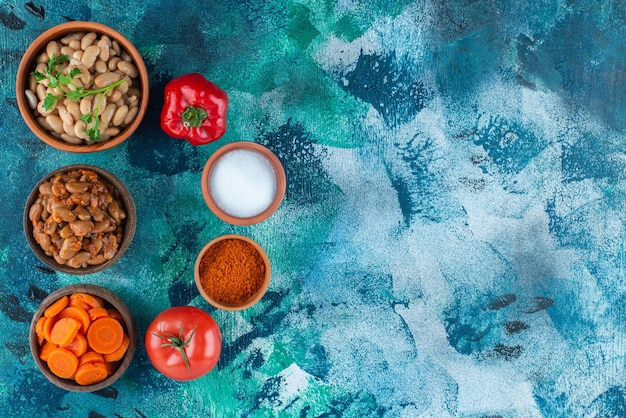 Przepyszna fasolka po bretońsku w miskach z warzywami, na niebieskim stole.