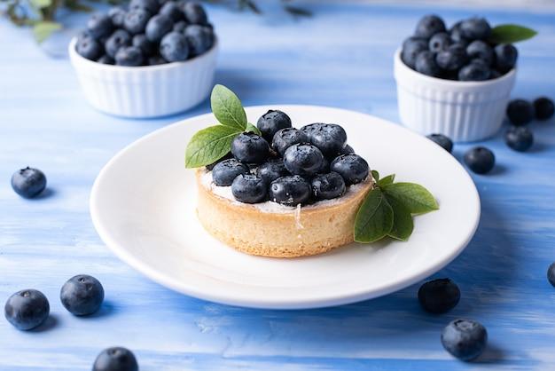 Przepyszne tarta z jagodami w białym talerzu na niebieskim tle, pyszny deser jagodowy.