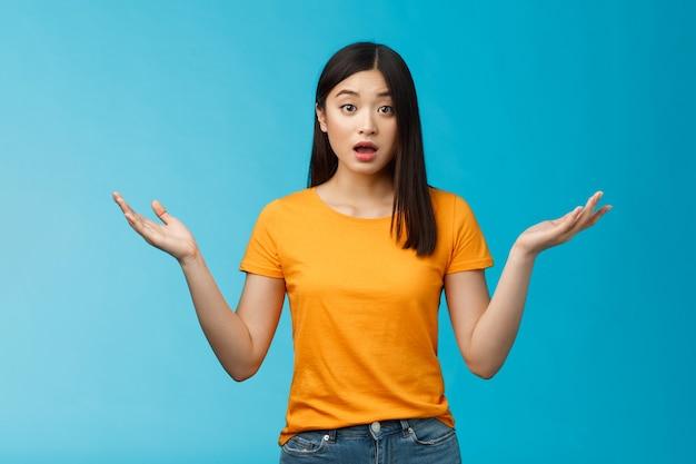 Przepytana, nieświadoma młoda azjatka z ciemną, krótką fryzurą, wzrusza ramionami rozłożonymi na boki, wygląda na zdezorientowaną, z otwartymi ustami jest niepewna, nie ma pojęcia, stoi na niebieskim tle i ma na sobie żółtą koszulkę.