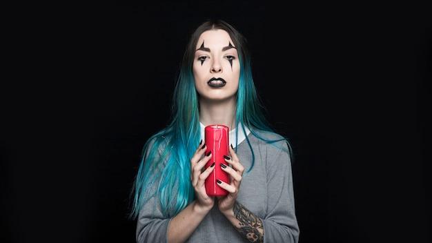 Przerażająca dziewczyna trzyma czerwoną świeczkę