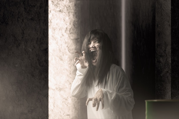 Przerażająca kobieta-duch z krwią i gniewną twarzą o szponiastych rękach prześladowała opuszczony budynek