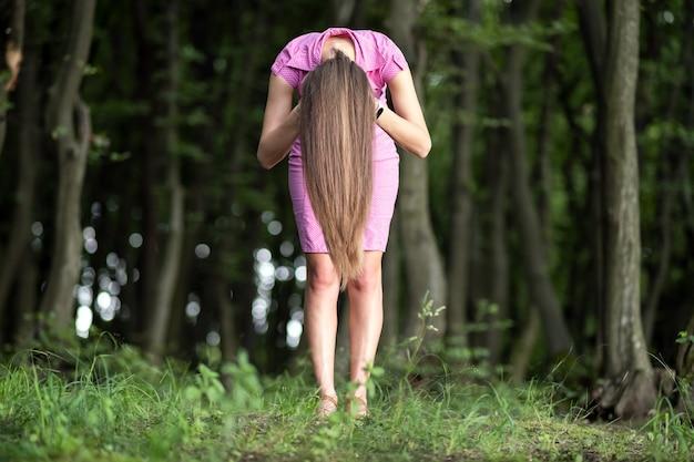 Przerażająca kobieta z długimi włosami pochyliła się w nastrojowym ciemnym lesie.