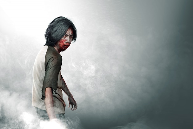 Przerażające zombie z krwią i raną na ciele chodzą pośród mgły