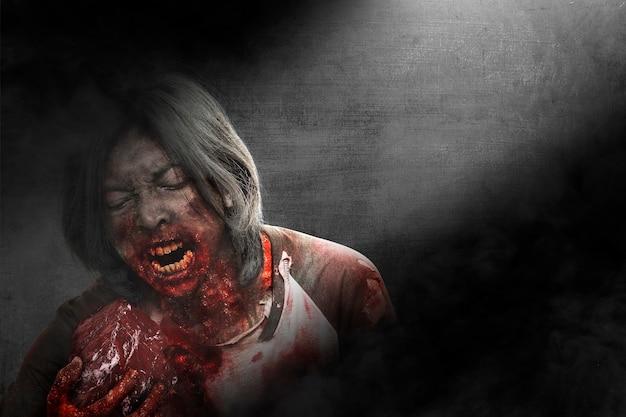 Przerażający zombie z krwią i raną na ciele zjada surowe mięso na ciemnym tle