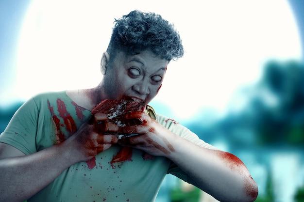 Przerażający zombie z krwią i raną na ciele zjada surowe mięso na tle nocnej sceny