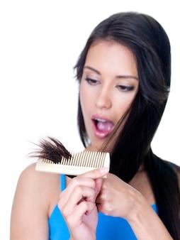Przerażenie na twarzy młodej kobiety patrzącej na niezdrowe końcówki włosów - odizolowane