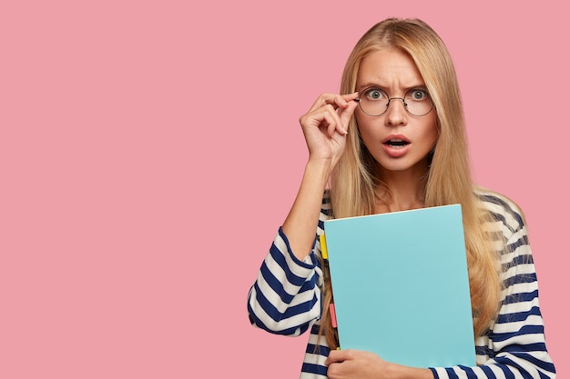 Przerażona blond studentka pozuje na różowej ścianie