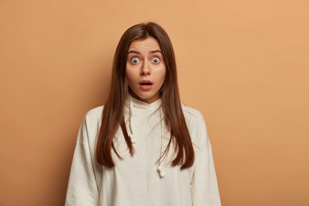 Przerażona dama wstrzymuje oddech od szoku, ma wyskakujące oczy, ma długie włosy, ubrana w białą bluzę, ma naturalny makijaż