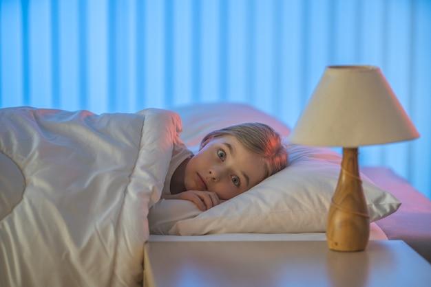 Przerażona dziewczyna leżała na łóżku. wieczorna pora nocna