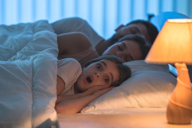 Przerażona dziewczyna leżała obok śpiących rodziców. pora nocna