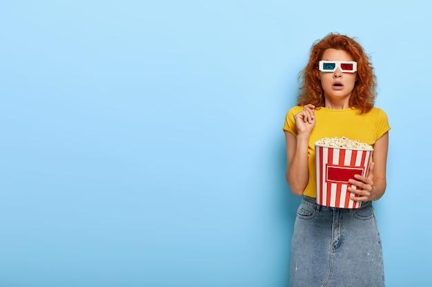Przerażona imbirowa urocza dziewczyna trzyma wiadro z popcornem