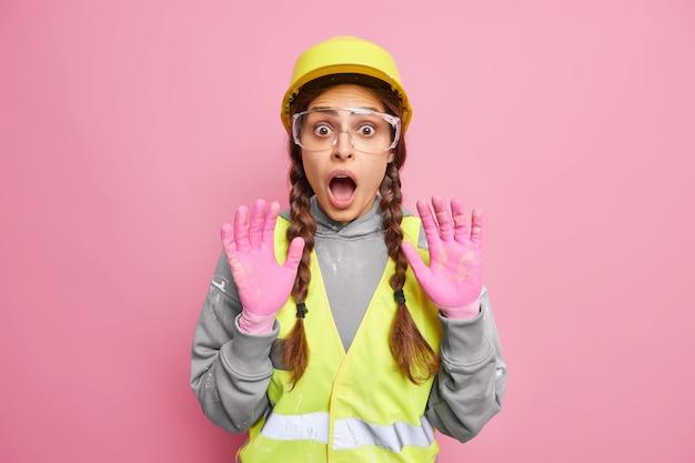 Przerażona inżynierka-konstruktor unosi ręce w rękawiczkach, boi się czegoś, dysząc ze strachu, nosi hełm ochronny i okulary, budując mundur na tle różowej ściany. pracownik przemysłowy