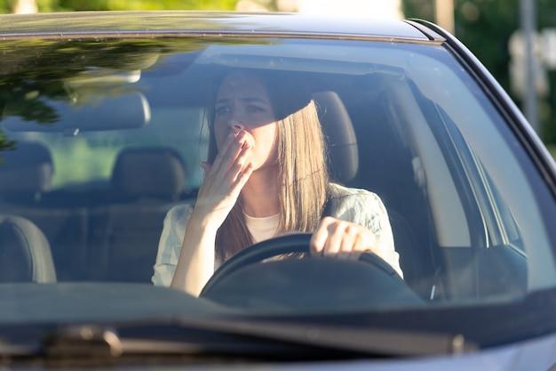 Przerażona kobieta, kierowca patrzy w lusterko wsteczne, przestraszona wypadkiem samochodowym, zestresowana dziewczyna w pojeździe