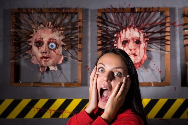Przerażona kobieta przed oskórowanymi twarzami na przerażającym miejscu zbrodni na halloween