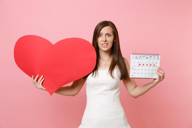 Przerażona kobieta w białej sukni, trzymająca pusty pusty kalendarz kobiet okresów z czerwonym sercem do sprawdzania dni menstruacyjnych
