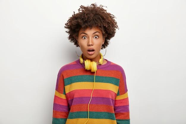 Przerażona kobieta z kręconymi włosami otrzymuje niesamowicie przerażoną informację, wytrzeszczają oczy, otwiera usta ze zdziwienia, nosi słuchawki stereo na szyi ubrane niedbale na białej ścianie