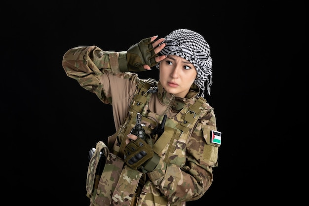 Przerażona kobieta-żołnierz w wojskowym mundurze z granatową czarną ścianą