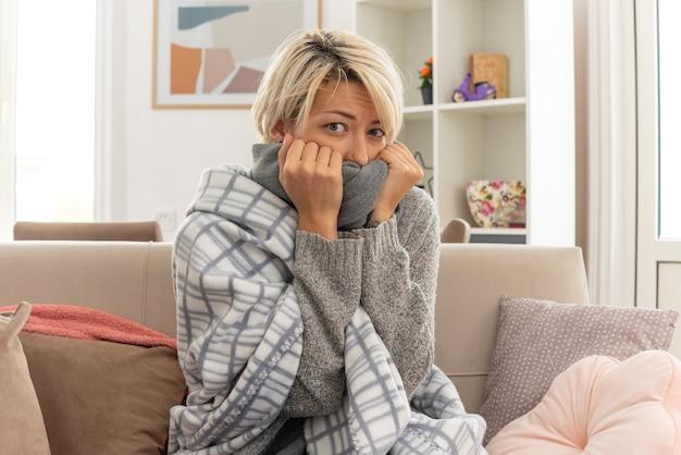 Przerażona młoda chora słowiańska kobieta owinięta w kratę zakrywającą usta szalikiem, siedząca na kanapie w salonie