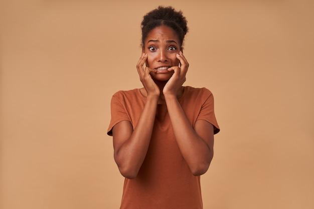 Przerażona młoda ciemnoskóra brunetka kobieta z fryzurą kok, trzymająca twarz z podniesionymi rękami, patrząc przestraszona, odizolowana na beżu