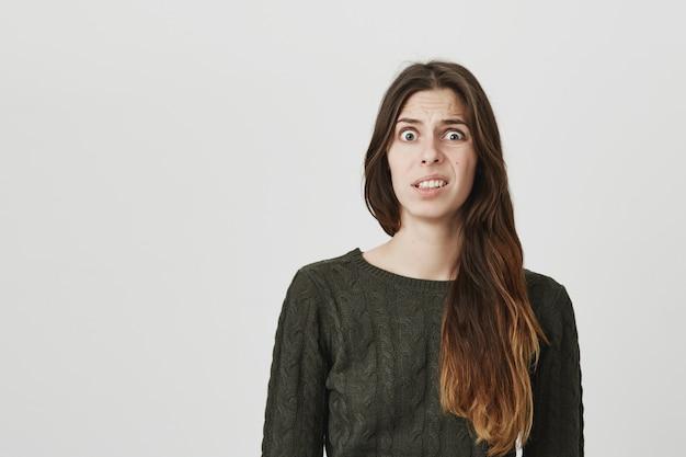 Przerażona młoda kobieta kuli się z powodu czegoś obrzydliwego lub dziwnego, krzywiąc się z niepokoju